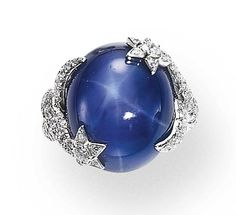 A STAR SAPPHIRE AND DIAMOND RING, BY CHANEL   Set with an oval double cabochon star sapphire, enhanced by circular-cut diamond stars, to the pavé-set diamond intertwined motif hoop, mounted in 18K white gold, size 6½, with French assay marks and maker's mark  Signed Chanel, 8G113