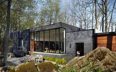 This dark brick home has made a life for itself in the forest