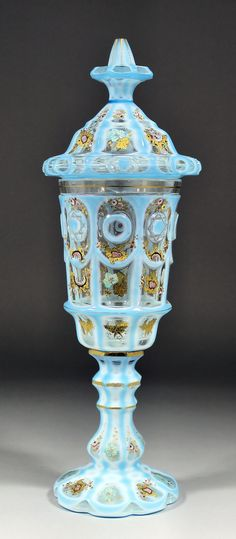 A 19th Century Bohemian pale blue opaque glass overlay and panel cut goblet and cover with gilt and coloured enamel decoration of vine leaves