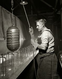 """February 1942. Akron, Ohio. """"Conversion. Beverage containers to aviation oxygen cylinders. Removal from solution tank at a rubber factory no..."""