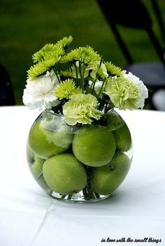 green apple centerpiece. Square vase with brown ribbon and white hydrangeas