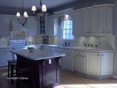 White cabinets & back splash with gray walls. I like the arch over the window