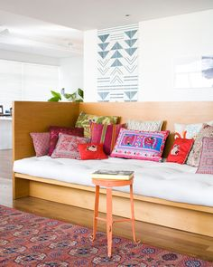 colorful pillows + wooden sofa/day bed. Alexandra approved. I would have drawers with pulls underneath for added storage.