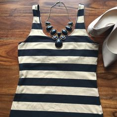 Banana republic striped tank Very versatile top with built in bra no padding. Black and Tan colored stripes. Photos definitely make the tan stripes look lighter. Wear and tear  throughout but no stains! Banana Republic Tops Tank Tops