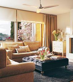 Salón con sofás en beige y puf tapizado en capitoné azul que funciona de mesa de centro