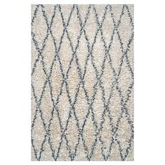 Add a touch of texture to your living room or den with this lovely shag rug, showcasing a diamond trellis motif for stylish appeal.