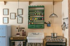 In the kitchen, retro touches such as a Smeg refrigerator and a burlap skirted farmhouse sink balance out the modern stainless steel range. RELATED: 11 Ways to Add Color to Your Kitchen   - CountryLiving.com