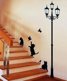 Рисунок котят, птиц и фонаря на стене у лестницы.