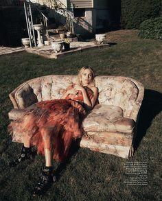 Posing on a sofa, Margot Robbie wears Alexander McQueen dress, belt and boots