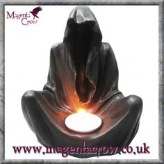 Final Flame Tealight Candle Holder Gothic Grim Reaper Candlestick. Features a dark hooded figure, Death the Grim Reaper. He sits cross legged with the tealight place in the inset on his lap. No face in the hood, just a dark void.