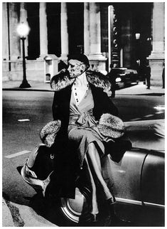 Model in a coat with wide fox collar and cuffs worn over silk wrap blouse and skirt by Gérard Pipart for Nina Ricci, photo by Helmut Newton, Winter 1973