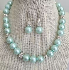 Mint green bridesmaid rhinestone pearl wedding jewelry set. This lovely jewelry set is designed with seafoam mint green glass pearls and stunning rhinestone ball beads. A gorgeous accessory for your special occasion! Perfect for Bridesmaids!  MATERIALS: ~ Glass Pearls measure 10mm ~ Rhinestone Ball Beads measure 8mm ~ High quality nylon coated 49 strand bead wire is used to ensure durability and long lasting wear. ~ A toggle clasp is used for a secure closure. ~ Hypoallergenic (Nickel Free)…