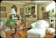 White armoire, tan armchair, brown/black table, ivy, flower prints.