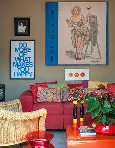 Muitos quadros cobrem as paredes da casa. Detalhe para o sofá da sala de Tv, que traz almofadas de todos os tamanhos e estilos (Foto: Divulgação/Romulo Fialdini)