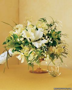 centerpiece with umbrella ferns, yellow-tinged euphorbia, itea dotted with buds, cattleya and mini cymbidium orchids, lilies of the valley, and jasmine vines. An eyelet wrap provides a sweet finish.