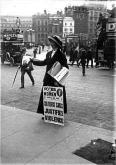 British suffragette with a poster, giving out newspapers