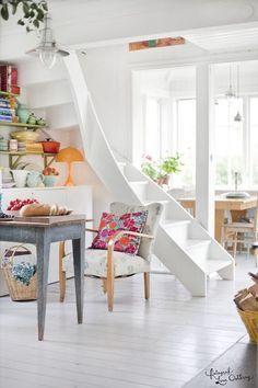 białe schody w centrum domu,białe kręcone schody z drewna w srecu otwartej zabudowy domu,jak zaaranżować otwatą przestrzeń z białymi schodam...