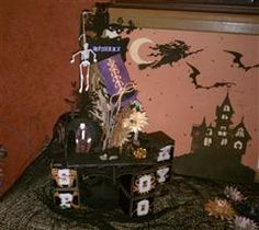 A Halloween table decoration.  Beetlejuice features a hanging skeleton, a vampire in his coffin, with several other featured characters from Happy Hauntings and October 31: a scarecrow, black cat, owl, flying bats and witch and sunflowers from Art Philosophy. #cricut
