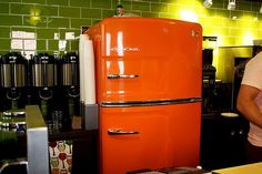 Retro Refrigerator in Orange brightening up a chic coffee shop. Avoid the normal 'white box' and bring some color into your kitchen with Big Chill #retroappliances #bigchill
