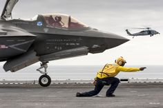 An F-35B test aircraft is cleared for short takeoff from the deck of the USS Wasp on Aug. 20, 2013. A helicopter supporting ship operations is in the background.