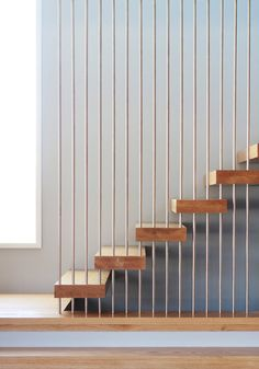 Dettaglio scala moderna con i tubolari d'acciaio che perforano i gradini in legno e arrivano dal soffitto fino al pavimento