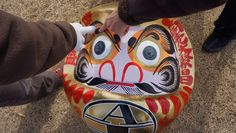 "It is easy to recognize a Takasaki daruma doll: the eyebrows are drawn to resemble a ""tsuru"" Japanese crane and the mutton chops to resemble a turtle--both considered good-luck augurs. (Louis Templado)"