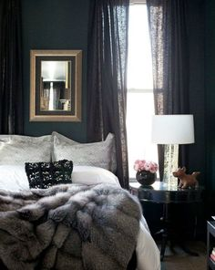Beautiful, dark and cozy bedroom painted black with white bedding and a gray faux fur throw blanket.