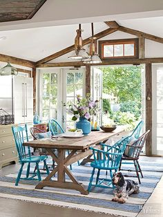"Vaulted cathedral ceilings accented with recycled barn beams lend a lofty air in this casual dining room. A farm table takes center stage among pale green floors and cabinetry. Turquoise dining chairs continue the ""comfort-above-all-else"" attitude. /"