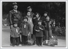 """Photo of the Mochida family awaiting the evacuation bus that will take them to a Japanese American Relocation Camp. Source: National Archives photograph; Wikimedia Commons. Read more on the GenealogyBank blog: """"World War II Japanese American Relocation Camp Newspapers."""" http://blog.genealogybank.com/world-war-ii-japanese-american-relocation-camp-newspapers.html"""