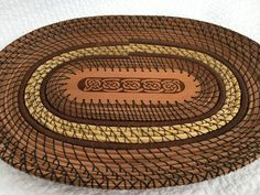 There is a beautiful Celtic knot pattern laser etched into an Alaska Red Cedar oval which is used for the center of this pine needle basket. The basket is shaped like a platter and measures 12 by 9. Natural colored tan pine needles give way to 3 rows of organic sweetgrass which is accented by cocoa colored wrapped rows. I have incorporated multiple stitches to give the platter an elegant look. The spiral wheat stitch is used to enhance the sweetgrass rows and the platter rim is topped off…
