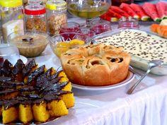 Mesa de café da manhã com variedades de pães, bolos, tortas, geleias, frutas e sucos