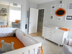 We love the orange pops of color in this gray woodland-inspired nursery!