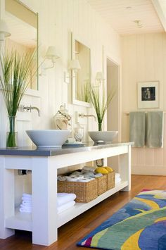 In this playful, contemporary bathroom, design Linda Humphrey places a pair of white porcelain vessel sinks atop a zinc covered vanity.