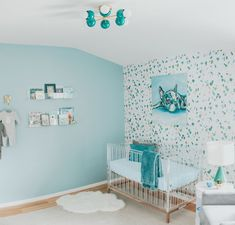 Mid Century modern teal nursery with a colorful flush mount ceiling light, faux terrazzo walls, and an acrylic crib.