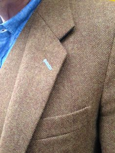 Close up detail of bespoke tweed jacket with light blue button hole detail.