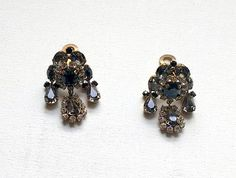 "Smoky crystal Austrian earrings chandelier rhinestone diamante clip on earrings. Stunning vintage statement Victorian revival earrings in gold tone metal.  These vintage smoky grey black crystal clip on earrings are likely to date from the mid 20th Century but are in a Victorian inspired style and are approximately 4½ cm, 1¾"" long.  Condition: The face of the earrings is in good vintage condition with slight wear in line with age. The reverse metal work has wear and marking (see image 4) the…"