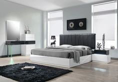 The design for this room has a beautiful, wooden floor and rug combination with the large, comfortable bed in the centre being accompanied by the two windows either side, allowing natural light to reflect from the stylish grey and white color combo. I love the mirror to the left that has a light beaming from the top.