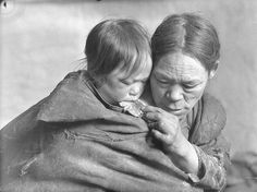 Padlemiut woman feeding caribou to a child at camp near Padlei, N.W.T.) [Kinaryuak (left) and Kipsiyak (right), 1950