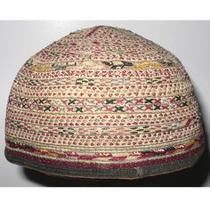 "TURKMEN BABY'S HAT  (ATHNB-103)  Central Asia. Mid-20th century      Turkmen child's skullcap, mid-20th ct. 15.5"" circumference x 4.5"" diameter x 3"" high,  Silk hand-embroidery on tan cotton;   a Turkmen mother (most likely from the Tekke tribe) made this little hat for her young child.  It was thought that a person's head was a particularly vulnerable place for evil spirits to enter, especially a child's head."