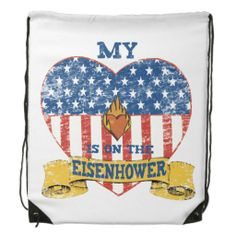 My Heart is on the Eisenhower Backpack | A drawstring backpack featuring a flag themed heart, a small heart with a flame, a gold banner, and the text, My Heart is on the Eisenhower. For those who have a sailor on the USS Dwight D Eisenhower aircraft carrier.