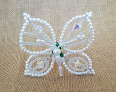 This beautiful Tapa Moño Tembleque is a mix of white flower and butterfly hair pins which will shimmer and tremble beautifully in your hair as you move. Each Tapa Moño hairpin is made with love and attention to detail with different shapes of white pearl beads, green pearle cotton floss, wire and sturdy 3 bobby pins. They will look great in your hair as cute accessory or complete your look with your Pollera Dress. Each tapa moño is 4.5 in width and 7.5 in length from front of butterfly near…