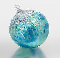 Tom Stoenner     Frosty blue-green colors dance over a blown glass globe, with iridescent chips of glass adding a sparkle of glistening texture.                                                                                                            Frosty blue-green colors dance over a  blown glass globe, with  iridescent chips of glass adding a sparkle of glistening texture.
