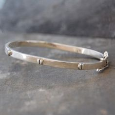Silver Raised Screw Bangle - This popular Silver Raised Screw Bangle is made up of two half oval forms of thick silver wire with silver screw head motifs protruding from the highly polished surface. #Otisjaxon #Jewellery