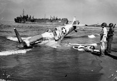 Supermarine Spitfire of the US 307th Fighter Squadron rests on the beach at Paestum Italy near Salerno after being shot down 9 September 1943. The pilot was uninjured. LST-359 unloads men and cargo beyond September 1943.