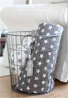 starred throws in a wire basket beside sofa
