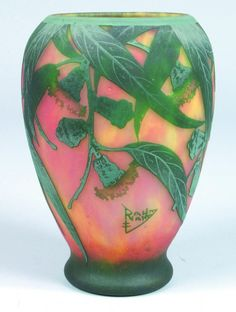Glass vase with green leaves on a pink and yellow ground by Daum