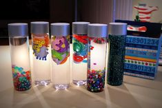 """Sensory Bottles - DIY . Need these for diaper changes!! ------------ Bought $.79 plastic bottles from Hobby Lobby, filled w/random things & water, hot glued the lids on. My son still plays w/them, they're awesome! However, if the items you put inside are not """"clean"""" or 100% water proof, they will make the water cloudy. Not as pretty but still effective!"""