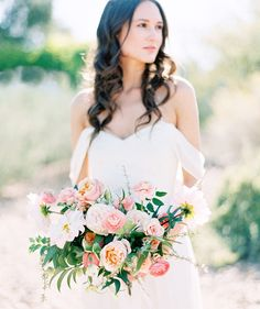 So pretty! Softly styled bride with loose waves and a bouquet of pink and coral flowers.