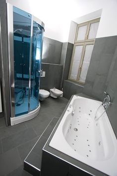 Gorgeous blue shower glass in this small modern bath.