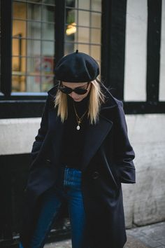 Emma Hill wears black beret, navy coat, black sweater, gold necklaces, high waisted jeans, chic outfit navy and black